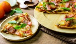 Rustic pizza with becon, salami, mozzarella and basil on wooden table